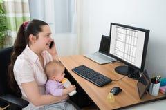Mulher com seu bebê que fala no telefone celular fotos de stock royalty free