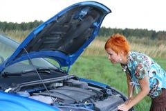 Mulher com seu carro quebrado. imagem de stock