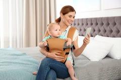 Mulher com seu filho no portador de bebê que usa o smartphone foto de stock royalty free