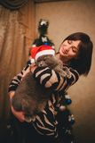Mulher com seu gato que veste o chapéu de Santa Claus perto da árvore de Natal Fotos de Stock Royalty Free