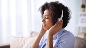 Mulher com smartphone e fones de ouvido em casa vídeos de arquivo