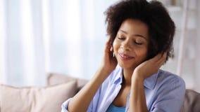 Mulher com smartphone e fones de ouvido em casa filme