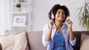 Mulher com smartphone e fones de ouvido em casa video estoque