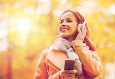 A mulher com smartphone e os fones de ouvido no outono estacionam Imagens de Stock