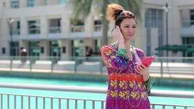 A mulher com smartphone e os fones de ouvido vermelhos escuta a música video estoque