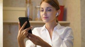 Mulher com smartphone para decolar fones de ouvido modernos video estoque