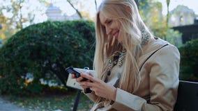 A mulher com smartphone relaxa em árvores de bordo do parque do outono Menina que senta-se no banco video estoque