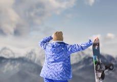 A mulher com snowboard olha na montanha da neve Fotografia de Stock Royalty Free
