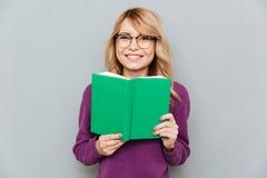 Mulher com sorriso do livro fotografia de stock
