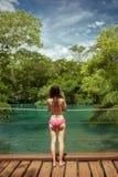 A mulher com suportes do biquini, e toma a imagem da cachoeira no bonito Imagens de Stock