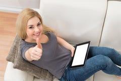 Mulher com a tabuleta de Digitas que mostra o polegar acima do sinal foto de stock