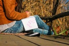 Mulher com tabuleta digital e notas na natureza - ame meu trabalho Fotografia de Stock