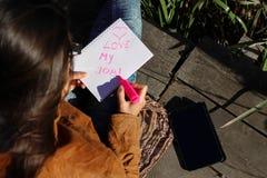 Mulher com tabuleta digital e notas na natureza - ame meu trabalho Imagem de Stock Royalty Free