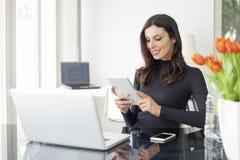 Mulher com a tabuleta digital no escritório foto de stock royalty free
