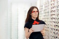 Mulher com a tabuleta do PC na loja ótica médica Imagens de Stock Royalty Free