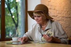 Mulher com tabuleta e dinheiro imagens de stock