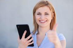 Mulher com tabuleta e os polegares digitais acima Imagens de Stock