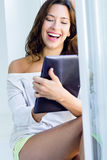 Mulher com tabuleta em casa Imagens de Stock