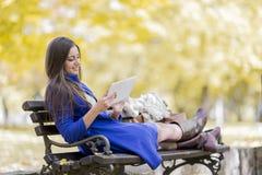 Mulher com a tabuleta no parque Imagens de Stock