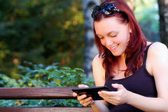 Mulher com a tabuleta no parque Fotografia de Stock