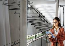 mulher com tabuleta que projeta a escada do escritório com linhas onde ele que vai ser Fotos de Stock
