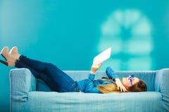 Mulher com a tabuleta que relaxa na cor do azul do sofá Fotografia de Stock