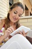Mulher com a tabuleta que senta-se em um sofá Foto de Stock Royalty Free
