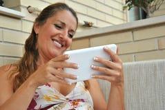Mulher com a tabuleta que senta-se em um sofá Fotografia de Stock