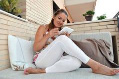 Mulher com a tabuleta que senta-se em um sofá Fotos de Stock Royalty Free