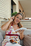 Mulher com a tabuleta que senta-se em um sofá Fotografia de Stock Royalty Free