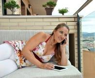 Mulher com a tabuleta que senta-se em um sofá Imagem de Stock