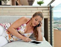 Mulher com a tabuleta que senta-se em um sofá Fotos de Stock