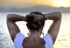 Mulher com a tatuagem traseira do cavalo marinho que está apenas de vista o horizonte de mar Imagens de Stock