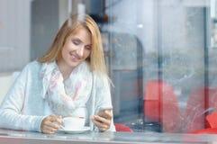 Mulher com telefone celular bonito do uso do sorriso ao descansar após o dia do trabalho no café fotos de stock royalty free