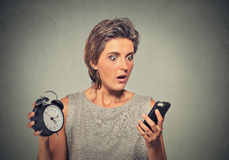 A mulher com telefone celular e despertador forçou o corredor tarde imagens de stock royalty free
