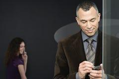 Mulher com telefone celular e homem com computador handheld fotos de stock royalty free