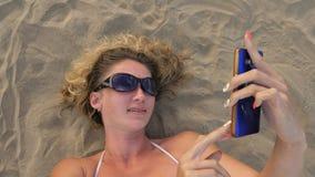 Mulher com telefone celular na praia vídeos de arquivo