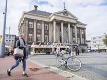 A mulher com telefone celular passa a câmara municipal de groningen nos Países Baixos foto de stock royalty free