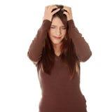 Mulher com terra arrendada da dor de cabeça sua mão à cabeça. imagem de stock royalty free