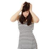 Mulher com terra arrendada da dor de cabeça sua mão à cabeça. Imagens de Stock