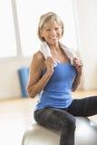 Mulher com a toalha em torno do pescoço que senta-se na bola da aptidão Imagem de Stock Royalty Free