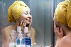 Mulher com a toalha no espelho próximo principal Imagens de Stock