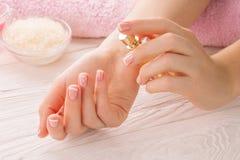A mulher com tratamento de mãos francês aplica o perfume no pulso Fotografia de Stock Royalty Free