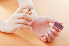 A mulher com tratamento de mãos francês do ombre aplica o perfume em seu pulso Scincare Cosméticos imagem de stock