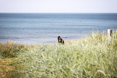 A mulher com trouxa deixa a praia Foto de Stock Royalty Free