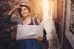 Mulher com trouxa e mapa na cidade velha no por do sol Imagem de Stock