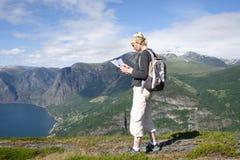 Mulher com trouxa e mapa nas montanhas Fotos de Stock
