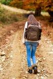 Mulher com a trouxa que caminha durante o outono Imagem de Stock Royalty Free