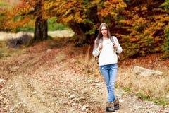 Mulher com a trouxa que caminha durante o outono Imagem de Stock