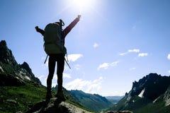 mulher com a trouxa que caminha na parte superior da montanha do nascer do sol fotografia de stock
